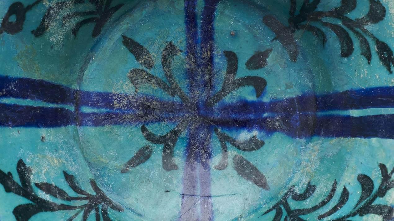 Détail coupe turquoise à composition cruciforme et tiges florales